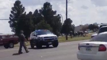 In this image made from video provided by Dustin Fawcett, police officers guard on a street in Odessa, Texas.
