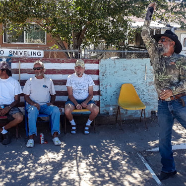 Eloy Valdez tosses a horsehoe watched by David Warne (centre on bench) and friends.