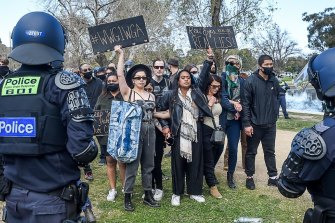 """A woman at an anti-lockdown rally in Melbourne holds up a sign with the hashtag """"#WWG1WGA"""", which stands for """"where we go one, we go all""""."""
