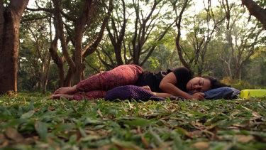 """A woman """"sleeping"""" in a park in Bangalore, in a protest aimed at reclaiming public spaces for women."""