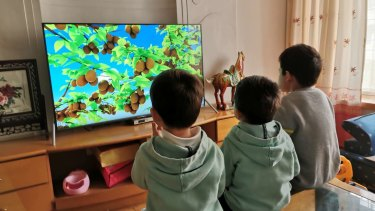 Gloria Zeng's children watch a video while under lockdown in Wuhan.