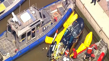 New York City police and fire departments work to secure a helicopter to the dock after it crashed in the Hudson River.