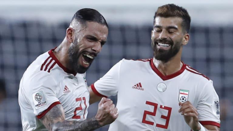 Iran midfielder Ashkan Dejagah, left, celebrates after scoring against Yemen despite being hampered by injury.