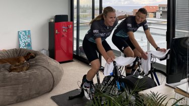 Cyclists Natasha (right) and Holly Cogle ride an indoor Zwift session at their Little Bay home.