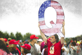 A Donald Trump supporter holds up a QAnon sign at a rally in 2018.