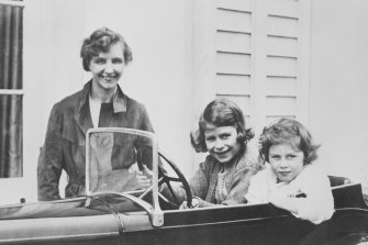 Princess Elizabeth and her younger sister Princess Margaret play in a miniature automobile while their governess, Marion Crawford, keeps an eye on them.