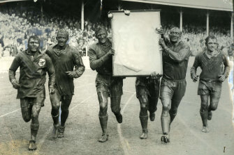 Captain Norm Provan and second-rower Kevin Ryan carry the J.J Giltinan Shield during St George's victory lap at the SCG in 1963.