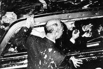 President Lyndon Johnson drives through the streets of Melbourne after his car was splattered with paint.