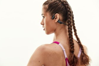 Aftershokz headphones use bone conduction pads in front of and behind the ear to provide sound.