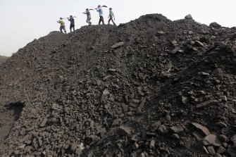 Workers walk on a heap of coal at a mine in the Mahanadi coal fields, India. Almost 40 per cent of India's electricity already comes from renewables but talk of a just transition is only starting to break through into the energy debate there, spurred on in part by health concerns over poor working conditions for miners.