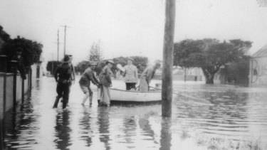 People get into a boat to escape the flood waters.
