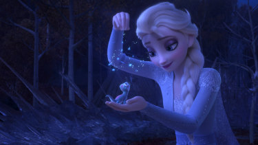 Elsa, voiced by Idina Menzel, sprinkling snowflakes on a salamander named Bruni in Frozen 2.