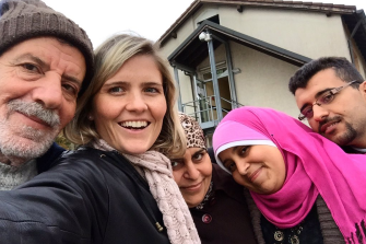 Sophie McNeill with Syrian refugee Nazieh Husein (left) and his wife and children in Germany. In her book McNeill tells of encountering Husein alone on the shores of Greece and helping him search for his family.