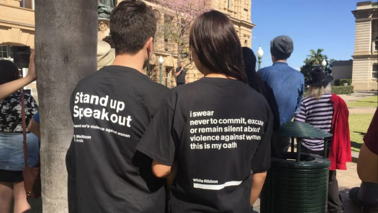 Men speak out against domestic violence on women at a rally in Brisbane's Queens Park.