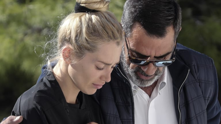 Viktoria Karyda, John Macris' widow, arrives at an Orthodox church for his funeral ceremony, south of Athens.