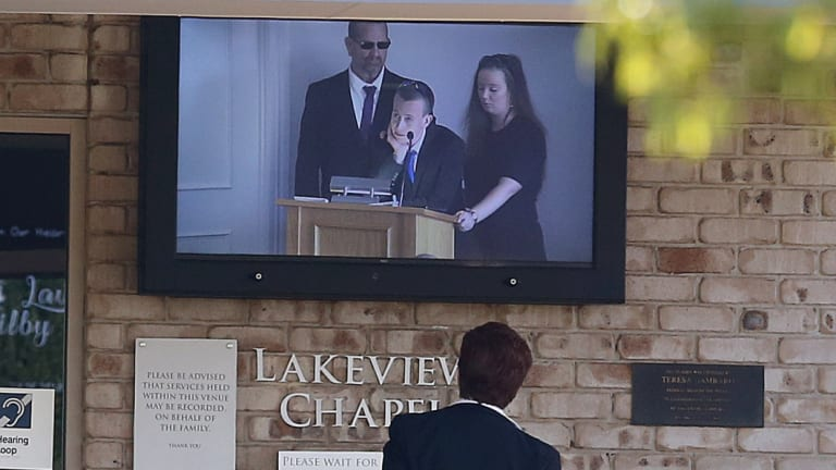 The father of slain Brisbane teenager Larissa Beilby, Peter (left), and sister Deanna (right) can be seen on a TV screen outside Lakeview Chapel during the memorial service.