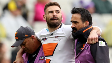 Giants star Stephen Coniglio is helped from the field on Sunday.