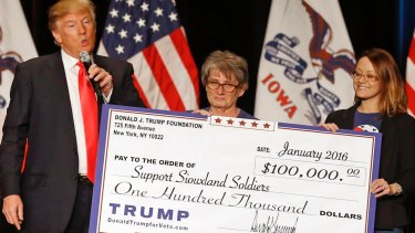 Donald Trump hands a giant cheque to Support Siouxland Soldiers during a campaign event in Iowa in 2016, one of several illegal payments made using charity funds.
