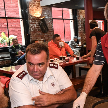 Salvation Army Major Brendan Nottle and Trevor Wulf check on a diner at Melbourne's Magpie Nest.