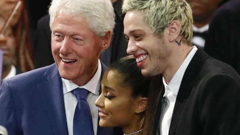 Former president Bill Clinton poses for a photo with singer Ariana Grande and her partner Pete Davidson during the funeral service.