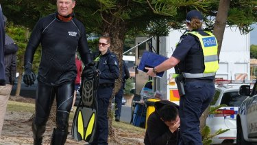 The distraught family of a snorkeller who went missing near the pier on Altona beach look on as the search and rescue team resumed on Sunday.