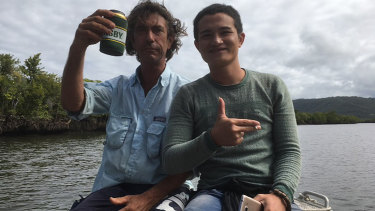 A local fisherman (left) treating one of two suspected asylum seekers to a tour after he was found on the banks of the Daintree River.
