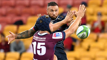 Prodigal son: Quade Cooper gets a kick away, past Hamish Stewart of the Reds at Suncorp Stadium.