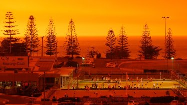 The fire above Port Macqurie turned orange and red on Friday night as bushfires tore through the area.