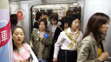 Women passengers get off a subway train at a Tokyo station.