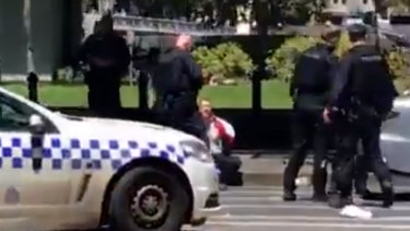 Police arrest a man at the corner of Flinders and Williams streets.