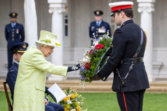 Major Thomas White, Equerry to the Queen, prepares to lay a wreath on her behalf.