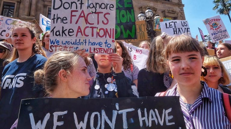 Students hold placards during Friday's climate protest in Melbourne.