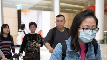 Passengers arrive at Sydney Airport wearing masks.