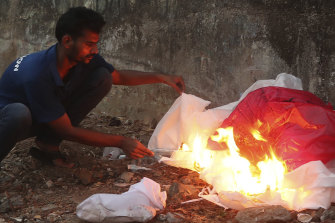 Izhaar Hussain Shaikh, left,burns his protective suit, after dropping a COVID-19 patient at a hospital in Mumbai.