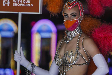 A showgirl wearing a protective mask promotes social distancing at the entrance to the Flamingo Las Vegas casino in Las Vegas, Nevada, U.S., on Thursday, June 4, 2020. All gaming venues in Nevada must follow strict protocols to account for Covid-19, including reduced capacity, more spacing on the casino floor and increased sanitation. Photographer: Joe Buglewicz/Bloomberg