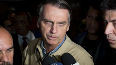 Presidential candidate Jair Bolsonaro, with the Social Liberal Party, talks to the press after visiting Federal Police headquarters in Rio de Janeiro,.
