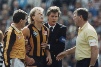 Dermott Brereton receives attention  after being flattened by Geelong's Mark Yeates in the 1989 grand final.