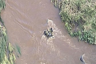 An emergency rescue team works to remove a ute from fast-moving floodwater in Canungra, amid the search for a missing man.