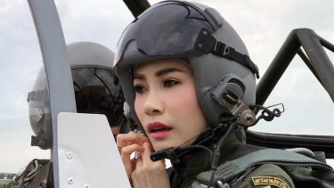 Thai Royal Noble Consort Sineenat Wongvajirapakdi adjusts her helmet in a military aircraft during training in Thailand.