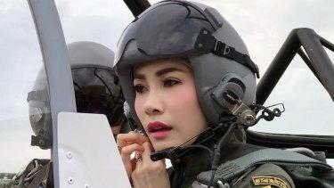Thai Royal Noble Consort Sineenat Wongvajirapakdi adjusts her helmet in a military aircraft during training in Thailand.