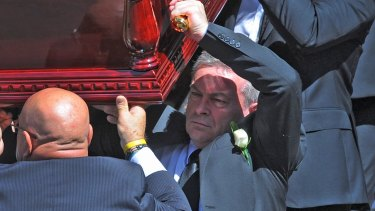 Borce Ristevski carries his wife's coffin.