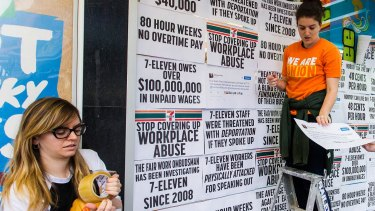 Protesters from the Young Workers' Centre pin signs to the windows of Melbourne 7-Eleven store highlighting the company's worker exploitation and wage fraud scandal.