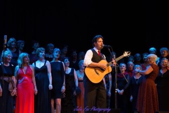 ABC broadcaster Nick Rheinberger singing here with Tina Broad (right) and Shoalhaven Mayor Amanda Finley (far right) part of the Glorious MUDsingers choir, who will appear in his rock opera, Watch and Act.