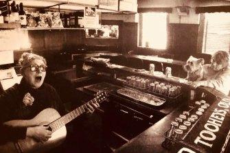 Doris Goddard plays guitar behind the bar at the Hollywood Hotel.