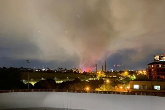 Smoke spreads over Sydney Park after a fire broke out at a motorcycle repair store in St Peters.