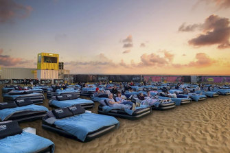 Beds, burgers, a bar and a big screen, on the beach.