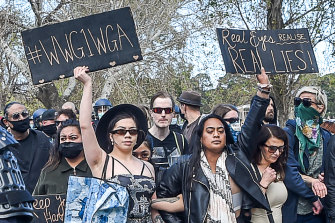 "An anti-lockdown protester in Melbourne's Albert Park in September holds a sign referring to the QAnon slogan ""Where We Go One, We Go All""."