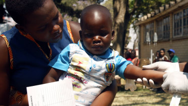 A health worker attends to a child suffering from cholera symptoms in Harare.