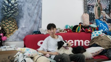 Zhou, 31, sits on the couch in his bedroom with 4 ½ -year-old Sylar.