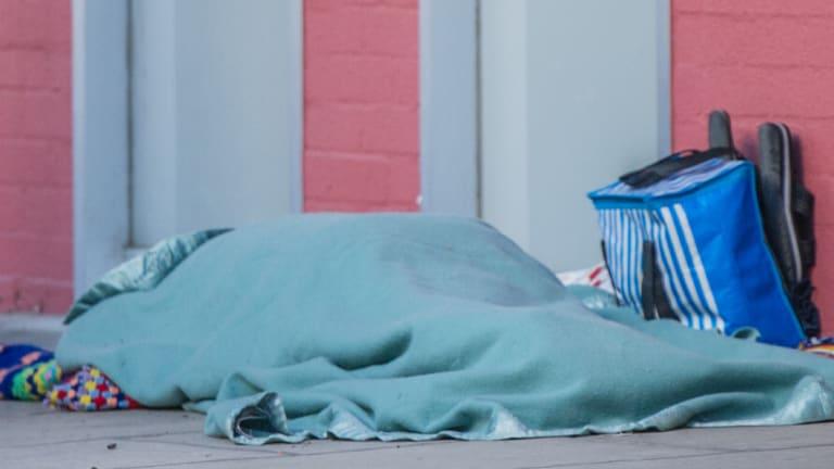 A homeless person sleeps rough outside the ACT Legislative Assembly.